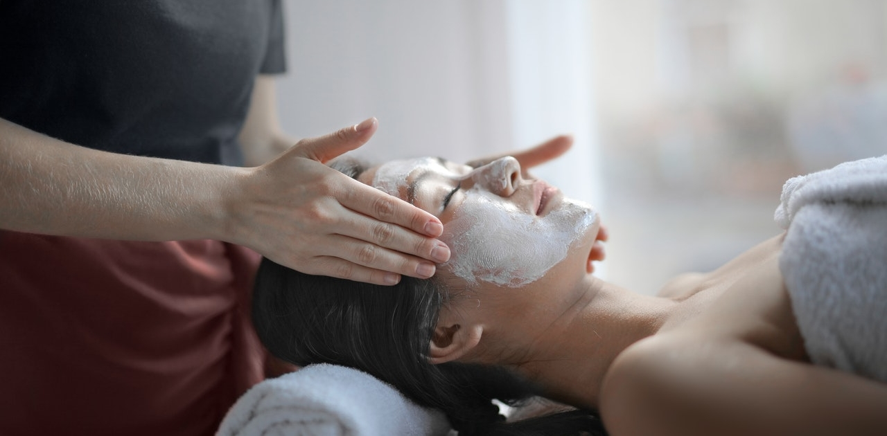 woman-smearing-facial-mask-spa-treatment